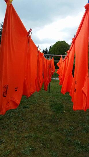 Die orangenen Laufshirts hängen frisch auf der Leine und warten darauf durchgeschwitzt zu werden